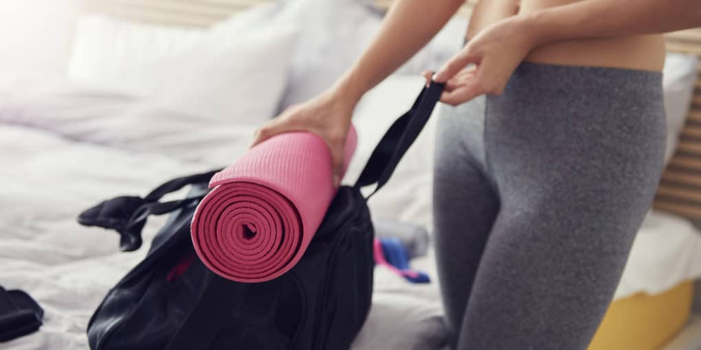Woman preparing gym bag with yoga mat holder