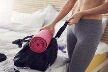 Woman preparing gym bag with yoga mat holder
