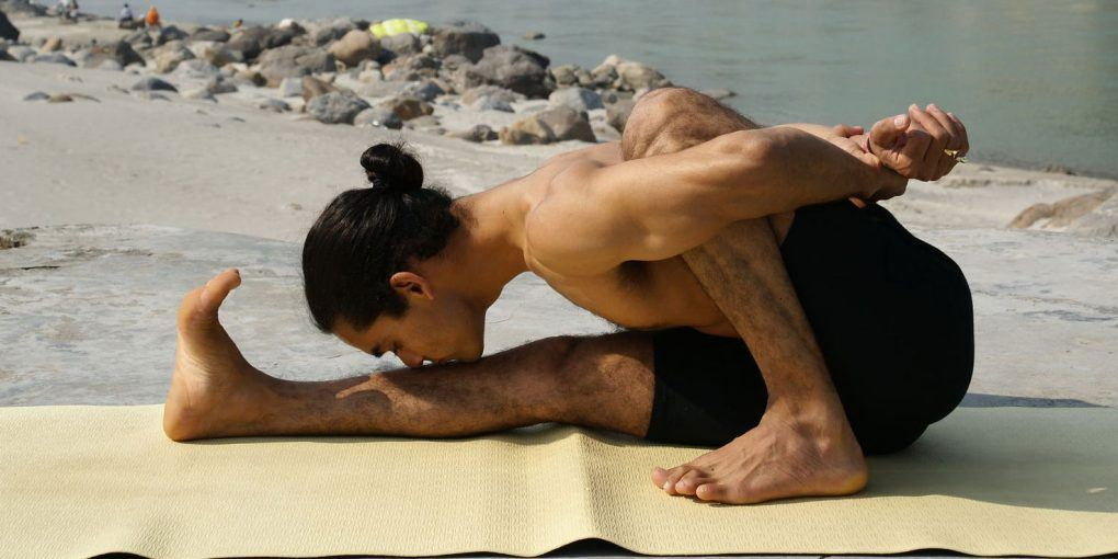 man practicing ashtanga yoga in front of lake