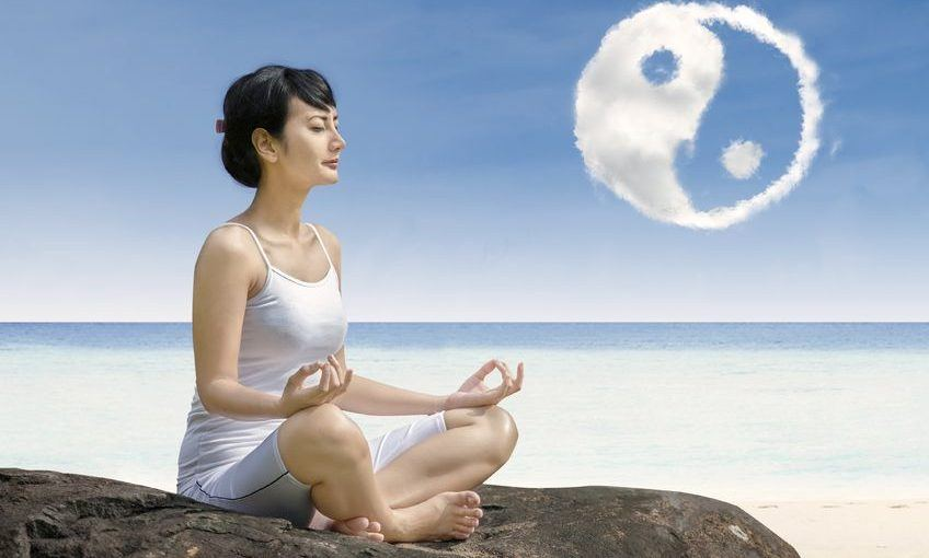 girl at beach doing yoga , under a ying yang cloud