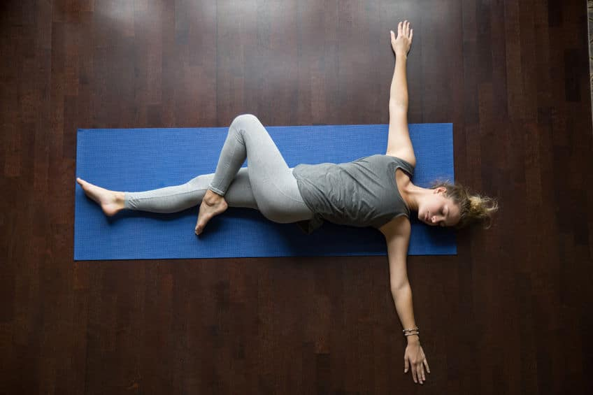 Woman Doing Spinal Twist Pose in Restorative Yoga