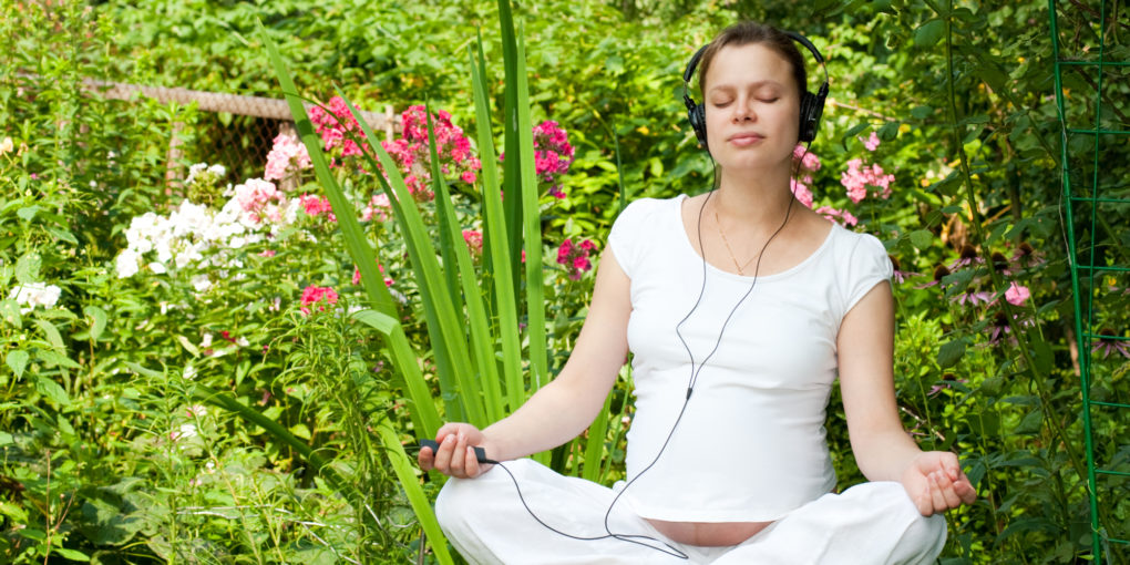 Young pregnant woman listening to binaural beats on headphones in garden