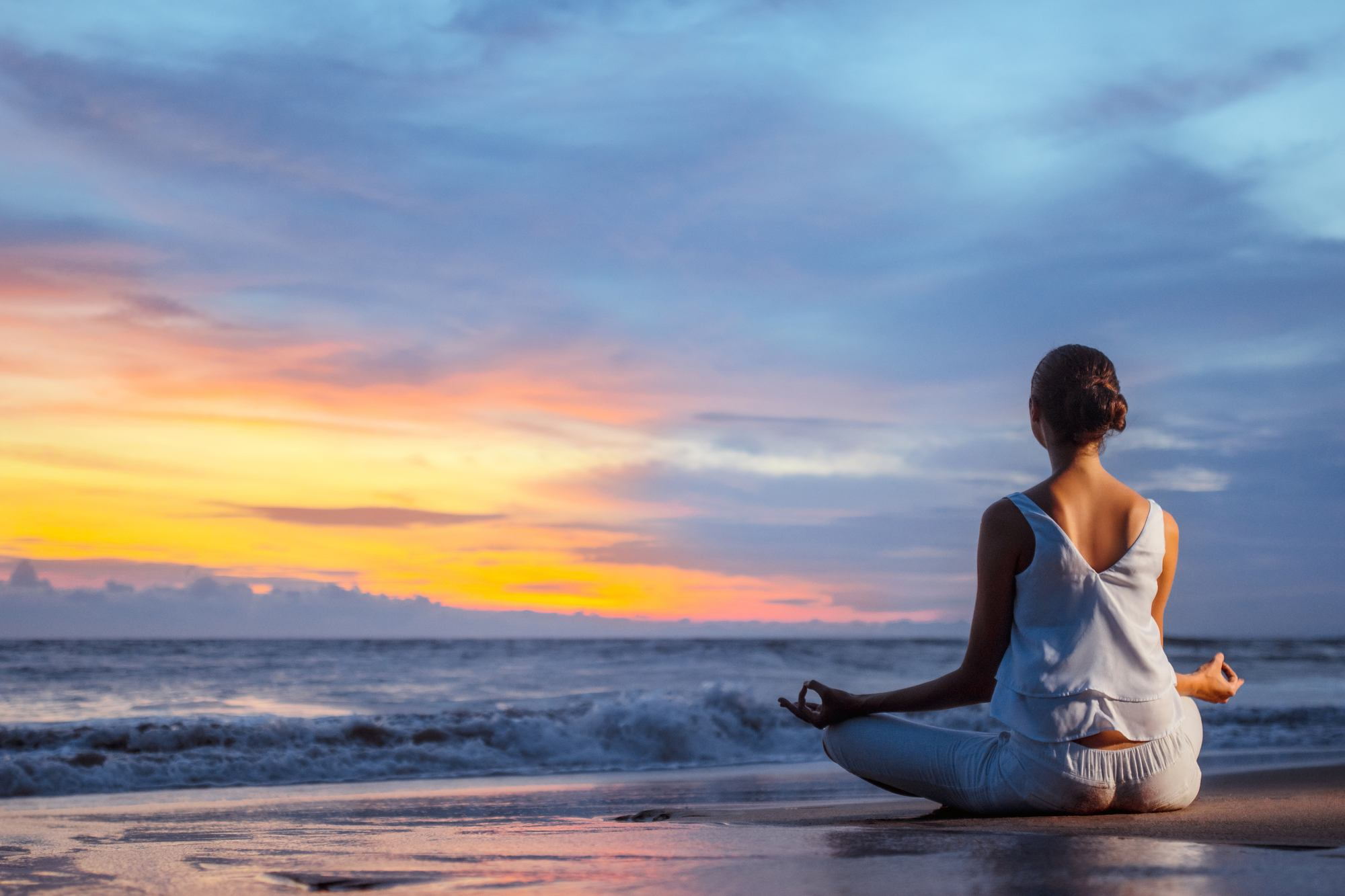 Young girl meditating in lotus pose on the beach