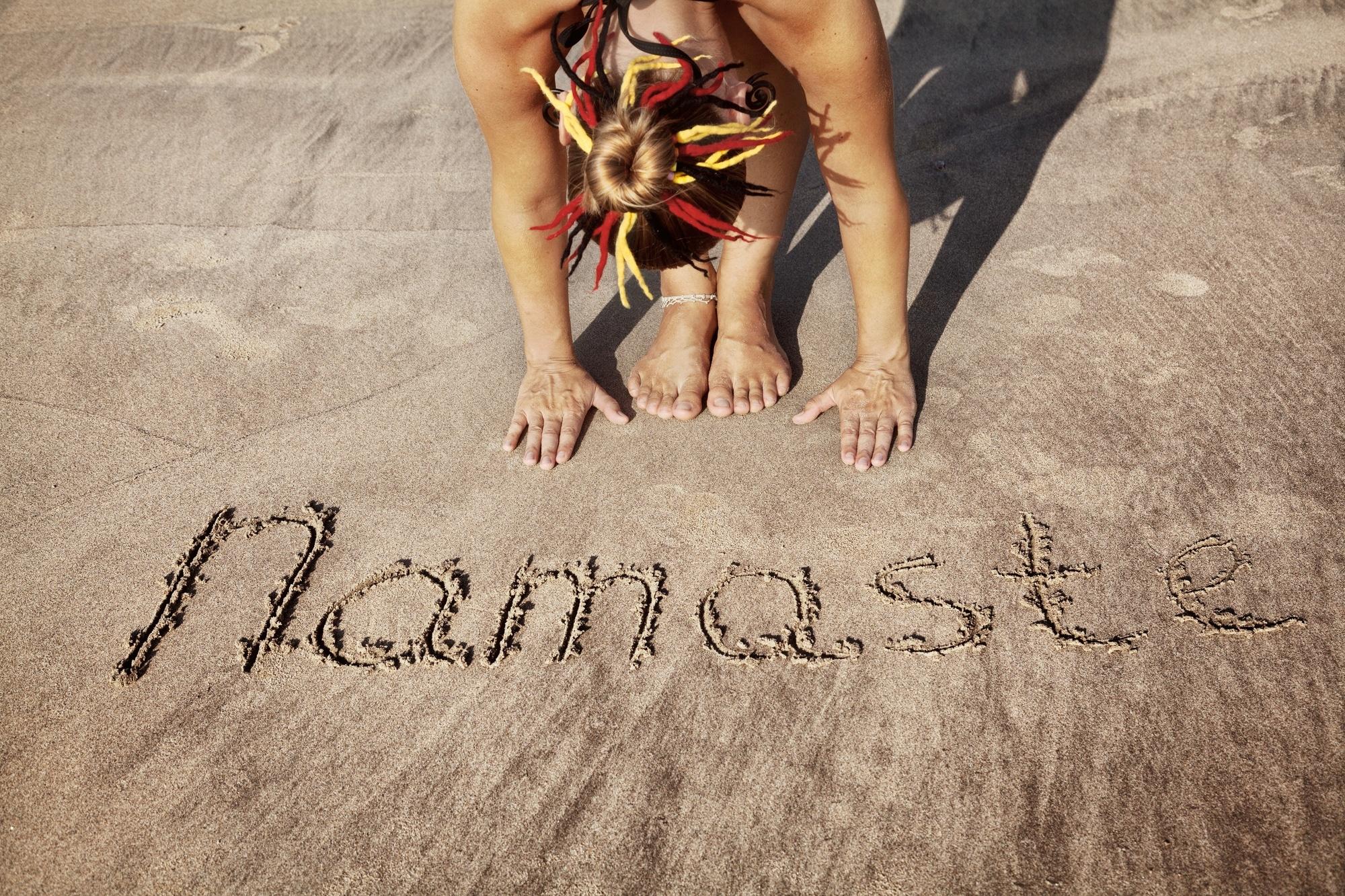 Woman doing yoga on the beach near Namaste handwriting in Goa, India