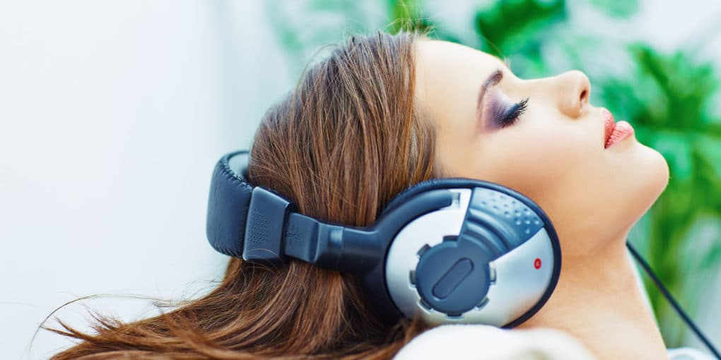 Young woman in lab listening to binaural beats on headphones as part of scientific study