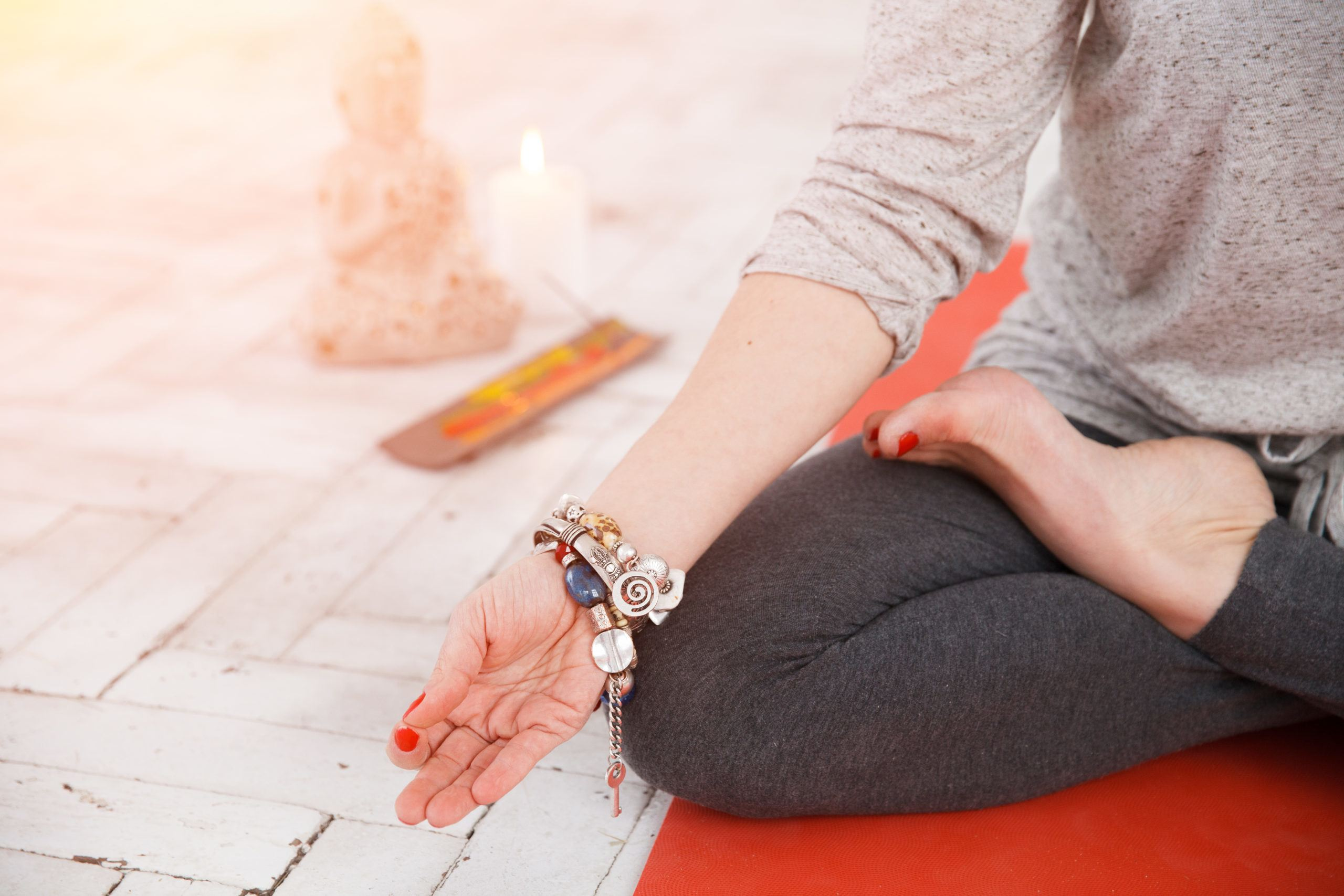 Woman sitting in lotus asana and doing grounding meditation with spiritual accessories, candles and Buddha statue.