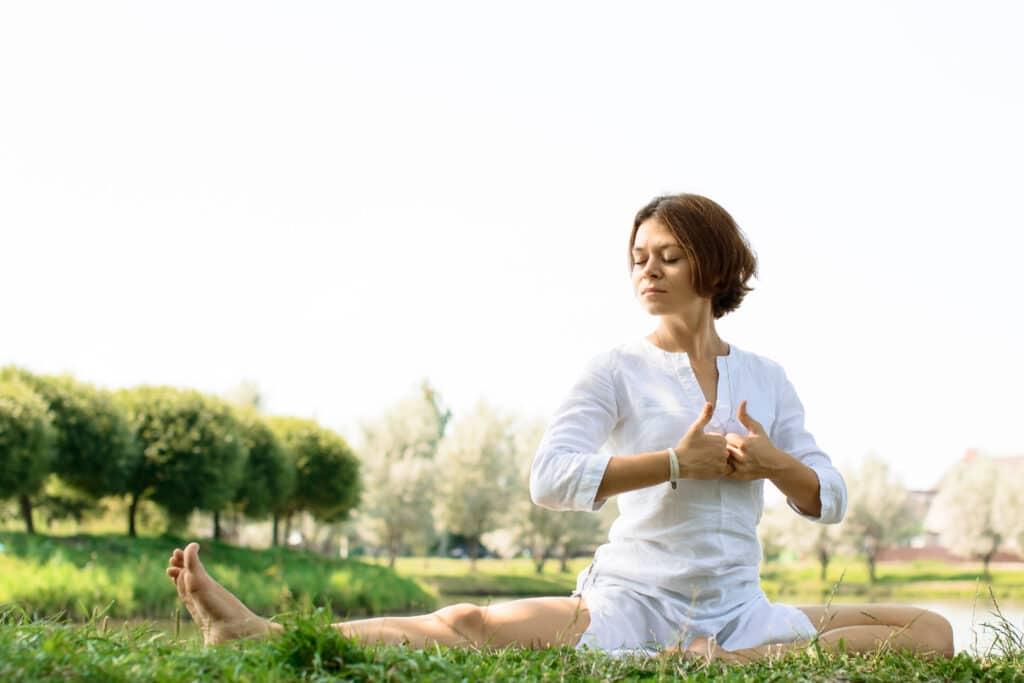 Woman practicing kundalini yoga meditation in park